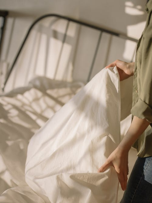 Person in White Button Up Shirt Holding White Textile