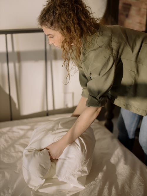 Woman in Gray Button Up Shirt and Blue Denim Jeans Sitting on Bed