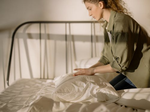 Woman in Gray Coat Sitting on Bed