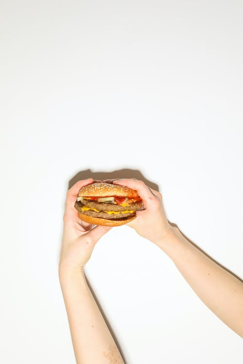Person Holding Burger With Patty