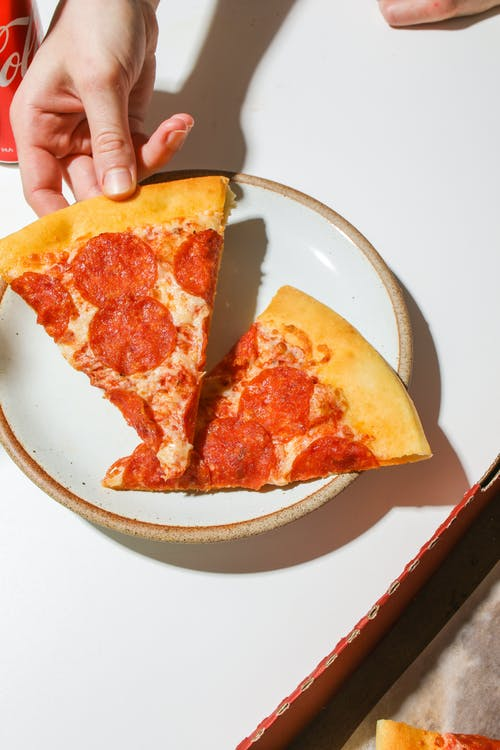 Person Holding A Slice Of Pizza On A Plate
