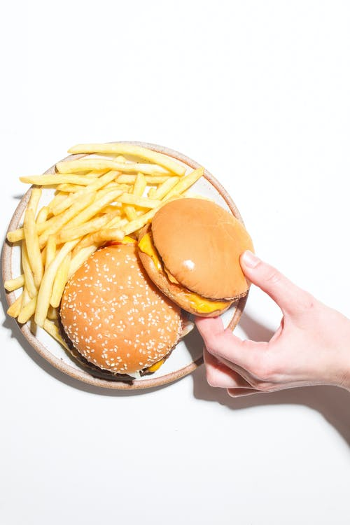 Person Holding Burger and Fries