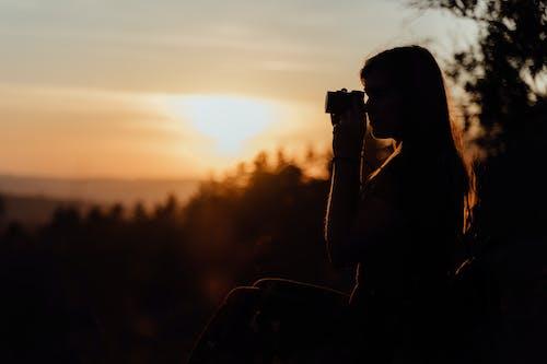 Woman in Black Tank Top Holding Black Dslr Camera during Sunset