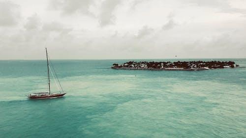 White Sail Boat on Sea Under White Sky