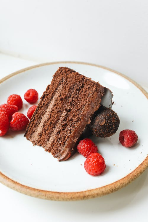 Delicious chocolate cake with raspberries on round plate