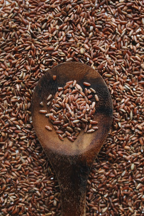 Close-Up Photo Of Brown Rice On Wooden Spoon