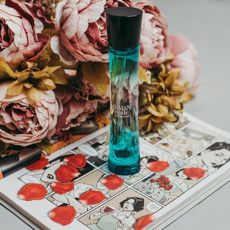 Blue Perfume Bottle On A Book Beside Flowers