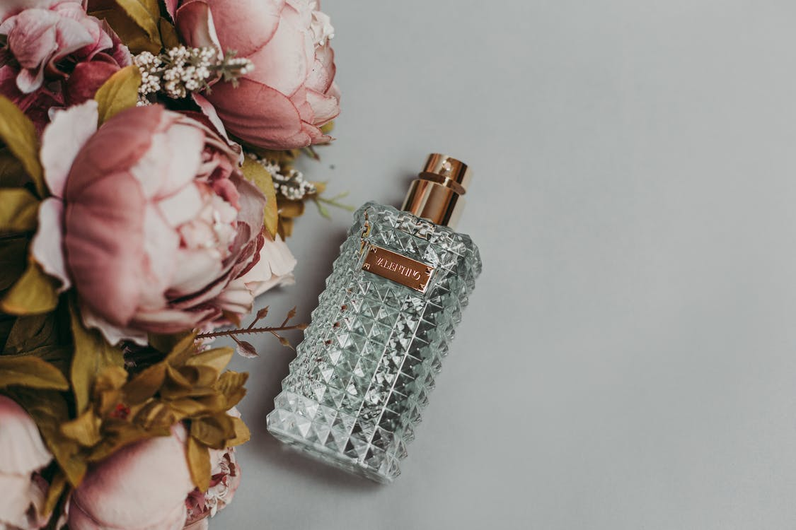 Photo Of Perfume Bottle Beside Artificial Flowers