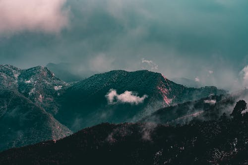 Majestic landscape of mountains covered with trees with snowy peaks under floating clouds on foggy day
