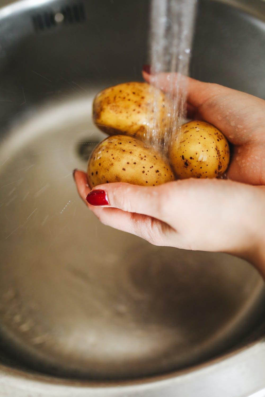 Person washing the potatoes. | Photo: Pexels
