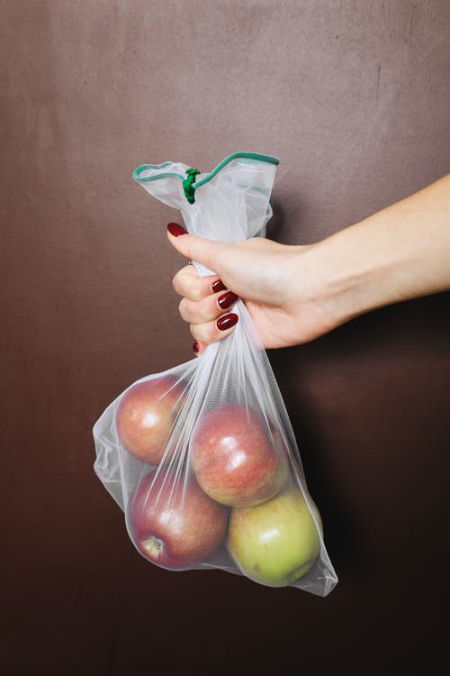 Photo Of Person Holding Bag Of Apples