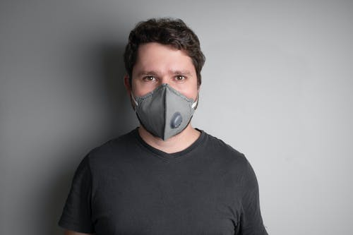 Man in Black Crew Neck Shirt Wearing White Face Mask
