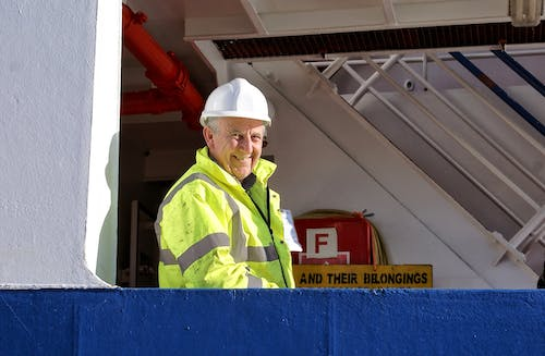 Elderly male technician smiling while working in industrial building