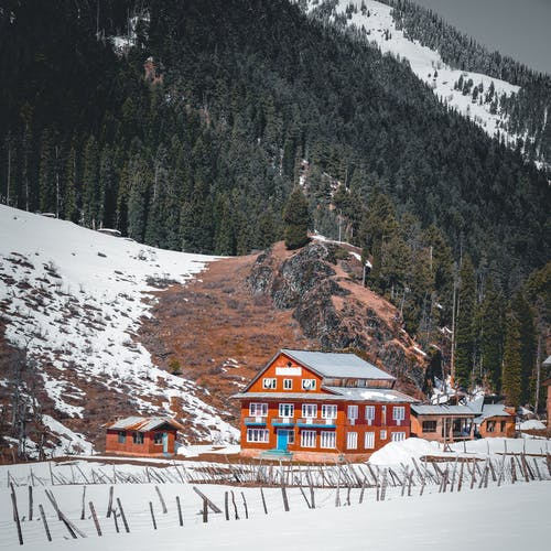 Brown Wooden House on Snow Covered Ground Near Mountain