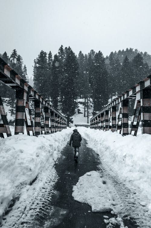 Person in Black Jacket Walking on Snow Covered Bridge