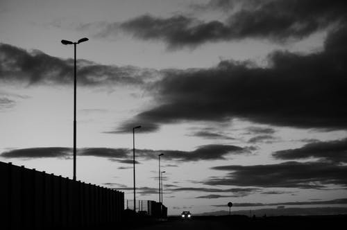 Low angle of black and white distant car with headlights riding on dark rural road near fences and streetlights against cloudy sky in evening