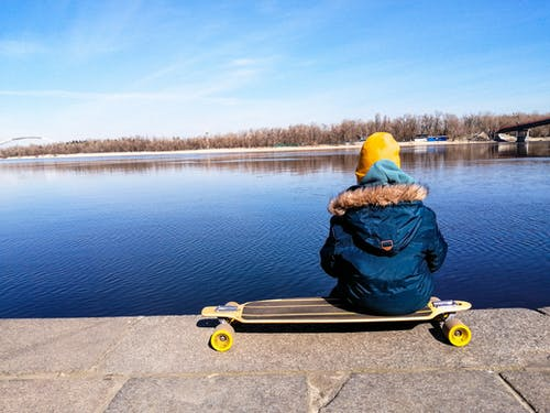 Person in Blue Jacket Sitting on Skateboard By The Lake