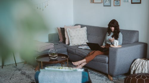 Photo Of Woman Sitting On Grey Couch