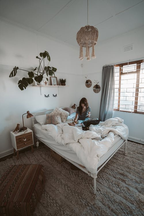 Photo Of Woman Sitting On Bed