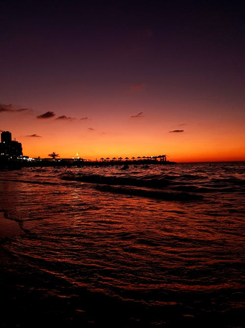 Sunset sky over waving sea and pier