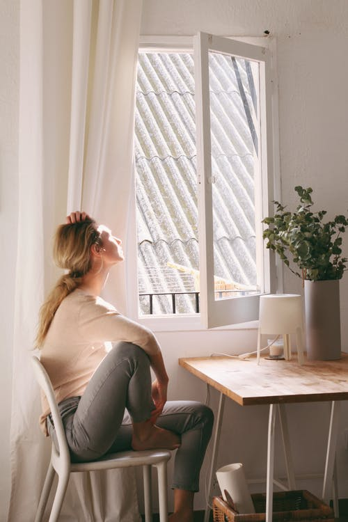 Mujer Sentada En Una Silla Junto A Una Ventana