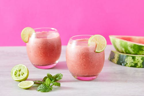 Clear Drinking Glass With Pink Liquid and Sliced Lemon