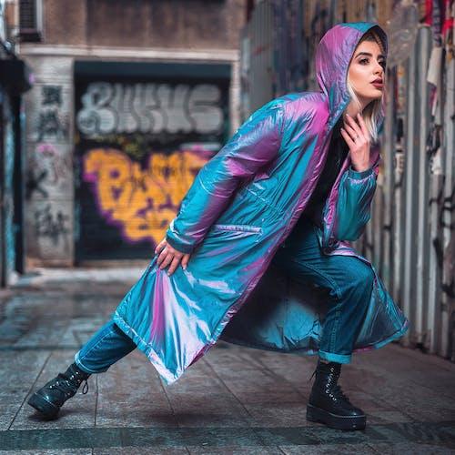 Stylish female in vibrant raincoat on street
