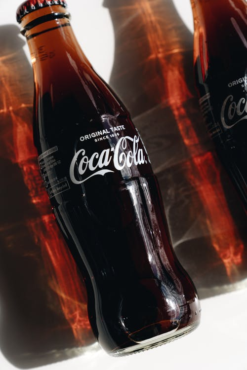 Coca Cola Bottle on Brown Wooden Table