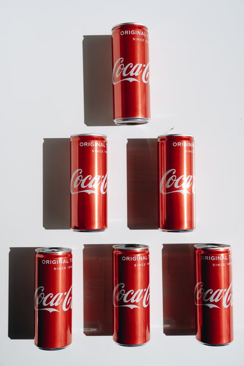 3 Coca Cola Cans on White Table