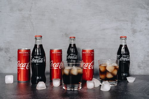 Photo Of Bottled Soft Drinks Beside Glasses