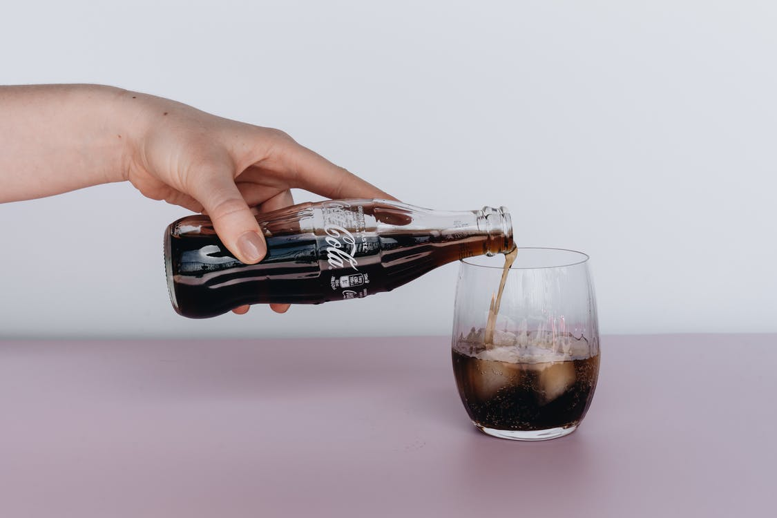 Photo Of Person Pouring Soft Drinks On Glass