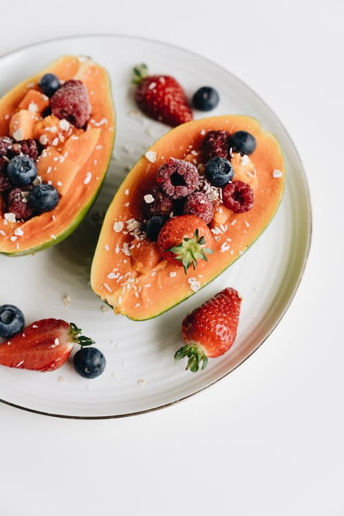 Close-Up Photo Of Sliced Papaya With Berries On Top