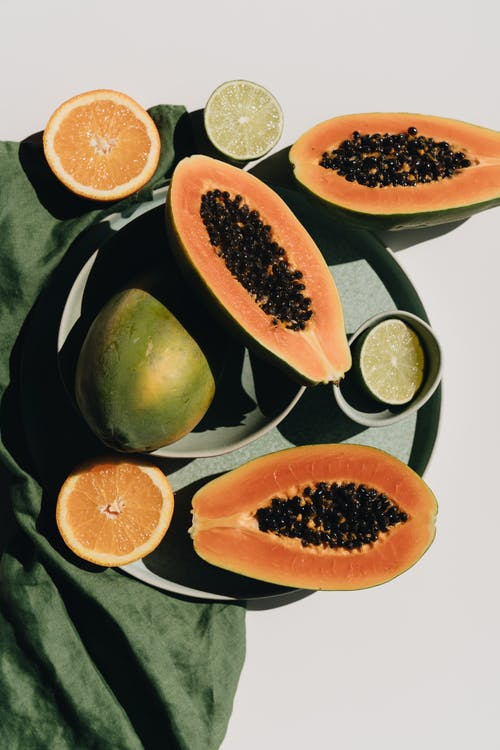 Top view of halves of ripe papaya together with oranges and limes placed on green round dishes and green fabric on white background