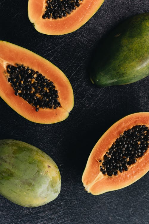 Top view of delicious ripe papaya halves and whole papaya placed on black wooden surface illustrating natural organic healthy food concept