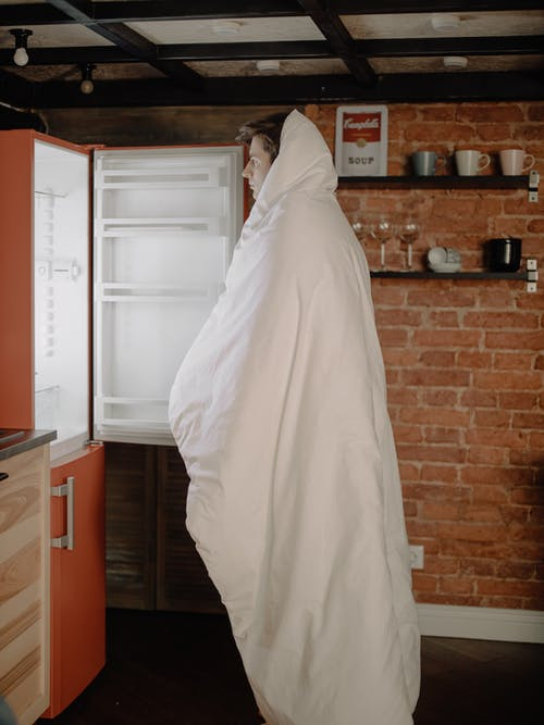 Woman in White Hijab Standing Near White Top Mount Refrigerator