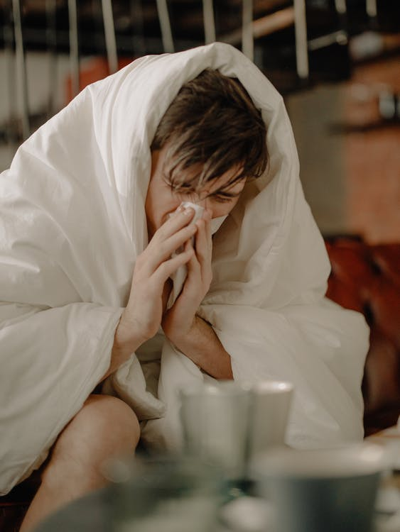 A Sick Man Wiping His Nose with Tissue