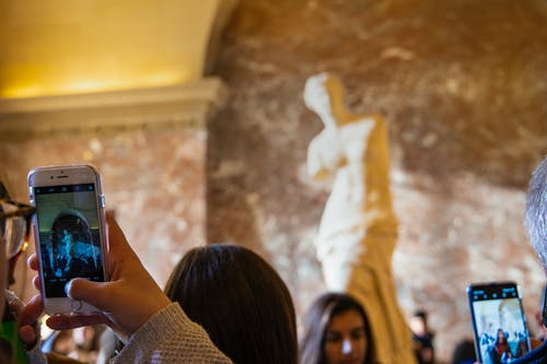 Faceless person taking photo of statue