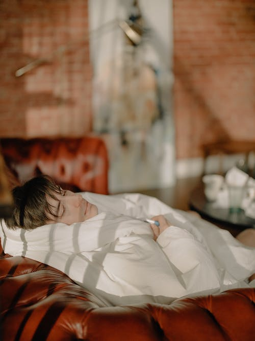 Woman Lying on Bed Covered With White Blanket
