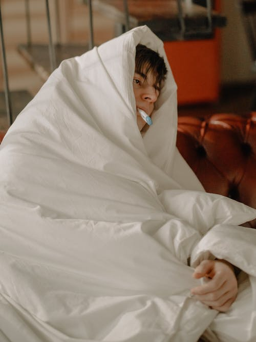 Woman in White Hijab Covering Her Face With White Blanket