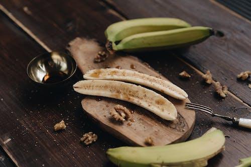 Peeled banana on wooden board with walnut