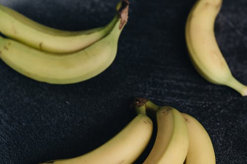 Ripe bananas on black wooden surface