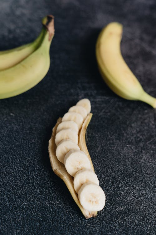 Ripe cut banana on black rough surface