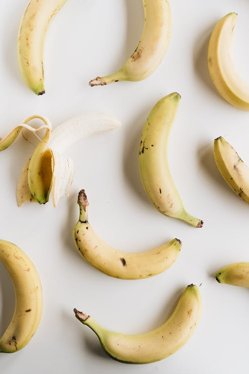 Top view composition of ripe half peeled banana among fresh yellow unpeeled bananas placed on white background under bright light