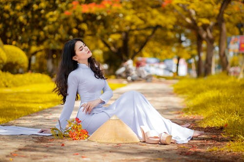 Woman in White Long Sleeve Dress Sitting On Paved Pathway