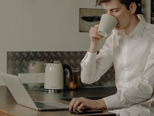 Man in White Dress Shirt Holding White Ceramic Mug