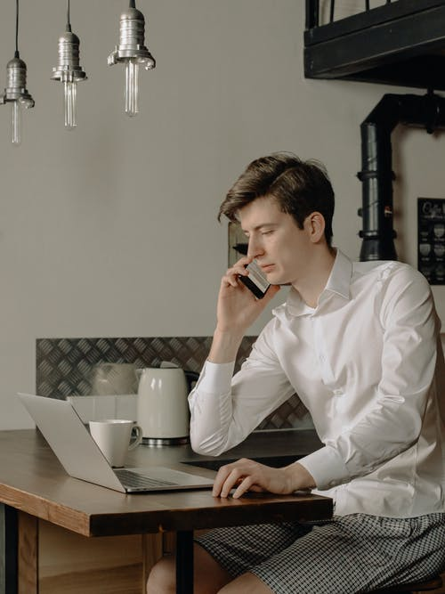 Man in White Dress Shirt Sitting at the Table