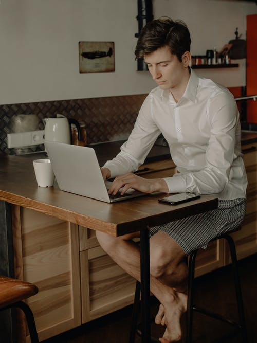 Woman in White Dress Shirt Sitting on Chair Using Macbook