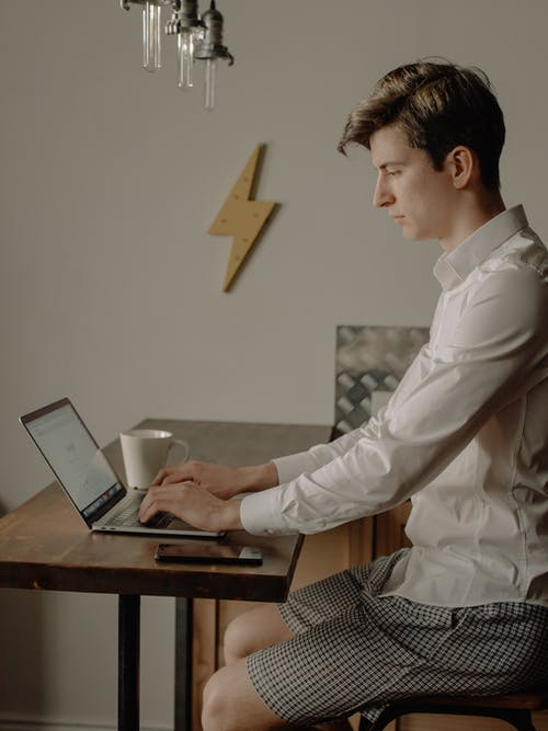 Man in White Dress Shirt Using Black Laptop Computer