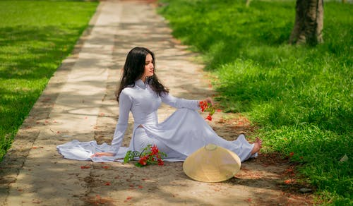 Woman in White Dress Sitting on Concrete Pathway