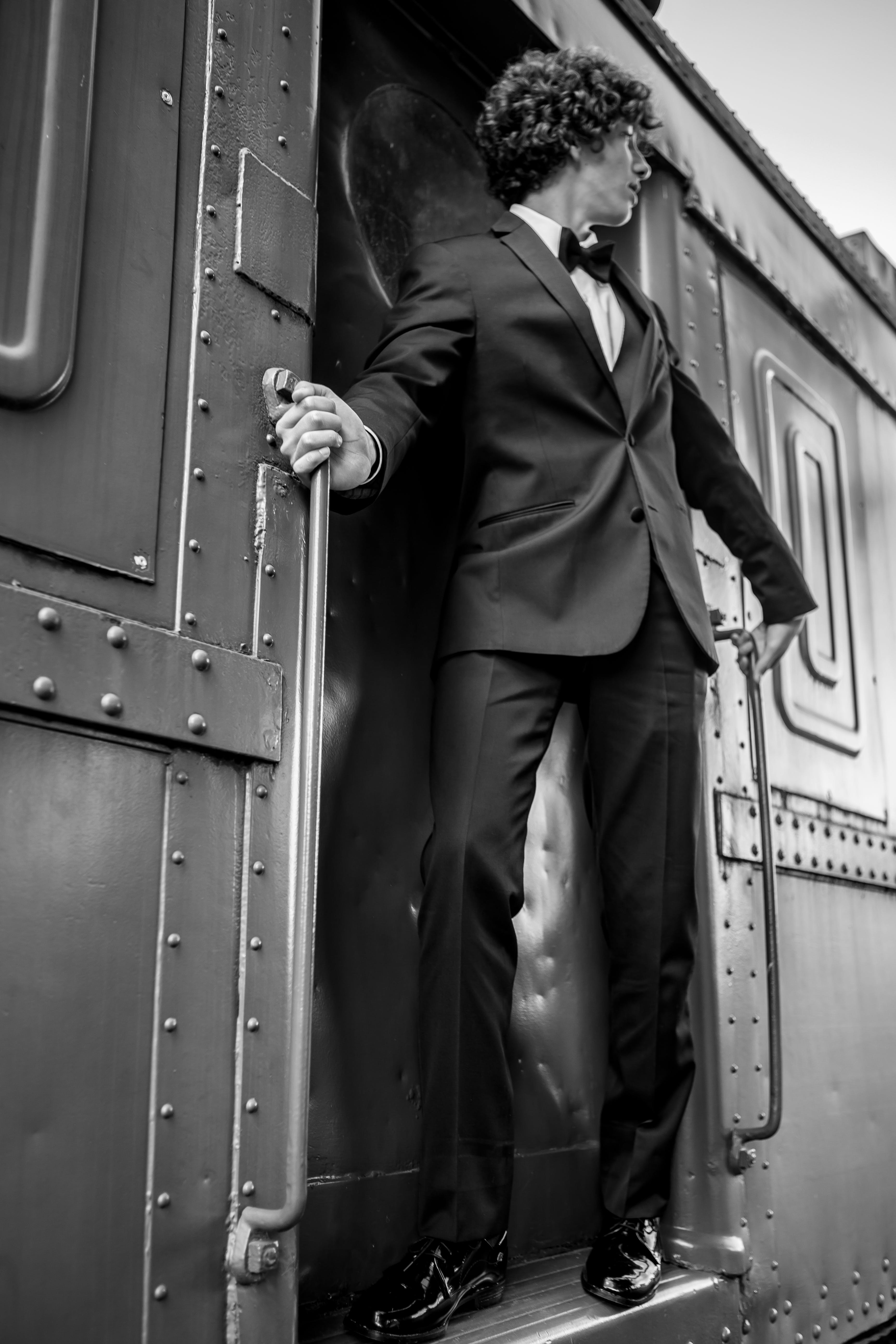 Grayscale Photography of Man Riding Train